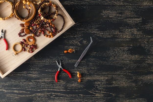 Bellissimo sfondo per seminari. strumenti per la creazione di gioielli, perline di pietra colorate e reperti in metallo.