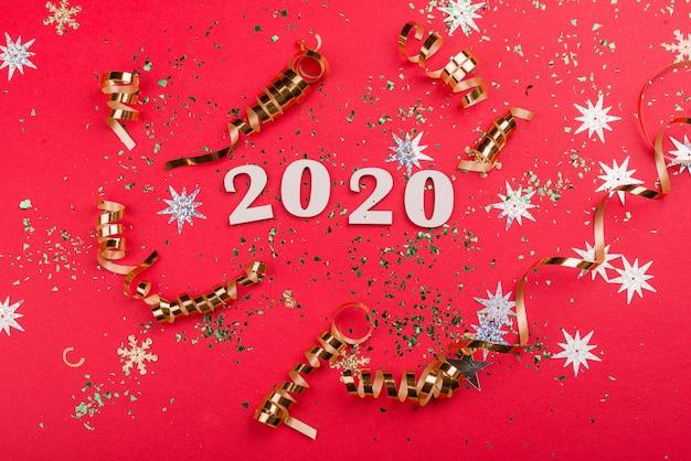 Bellissimo sfondo rosso festivo con scintillii e giocattoli d'oro di natale.
