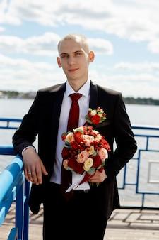 Bellissimo sposo amorevole con bouquet floreale