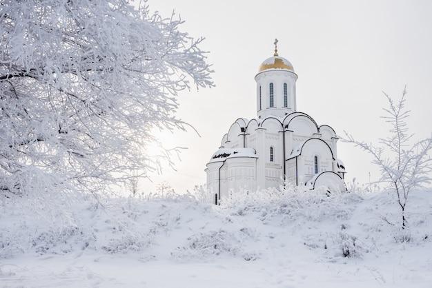 Bellissimo tempio bianco ortodosso tra alberi innevati