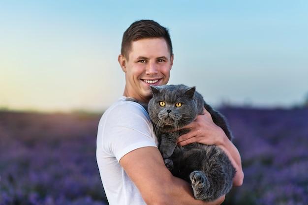 Bellissimo uomo con un gatto britannico nel campo di lavanda al tramonto. fantastica atmosfera estiva.