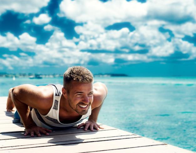 Bellissimo uomo muscoloso che si esercita in riva all'oceano. il fitness all'aperto estivo ti rende sexy e abbronzato.