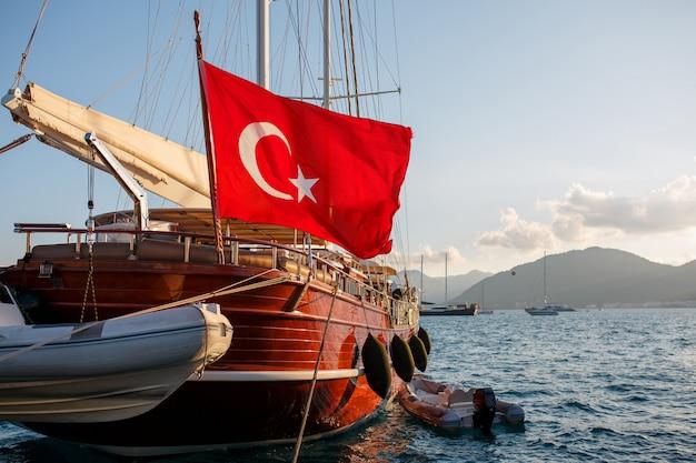 Bellissimo yacht in legno con la grande bandiera della turchia sul molo