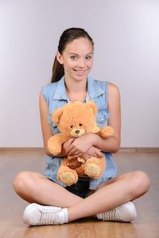Bello adolescente della giovane donna che si siede sul pavimento.
