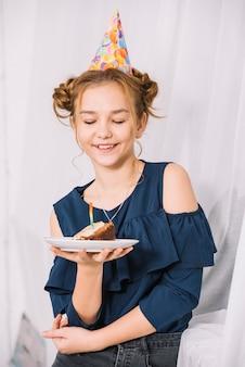 Bello adolescente sorridente che esamina fetta di torta sul piatto