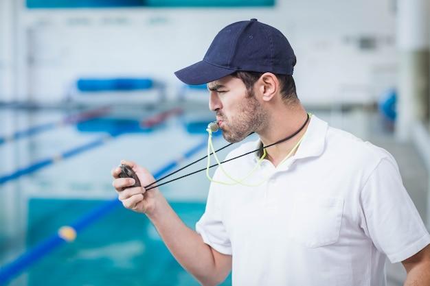 Bello allenatore che soffia fischietto e guardando il cronometro in piscina