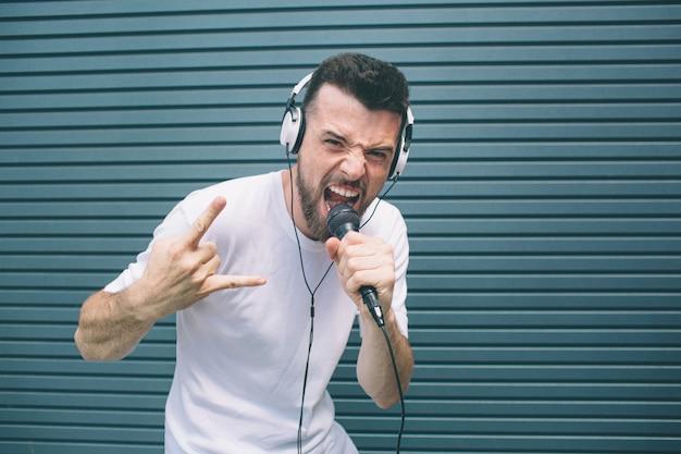 Bello amico è in piedi e in posa sulla macchina fotografica. sta urlando nel microfono e mostrando il segno cool. l'uomo indossa le cuffie. lui sta ascoltando la musica. isolato su strisce