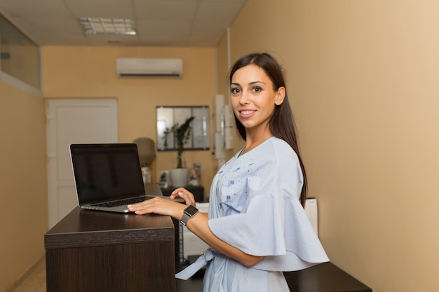 Bello amministratore della giovane donna alla reception che lavora al computer portatile.