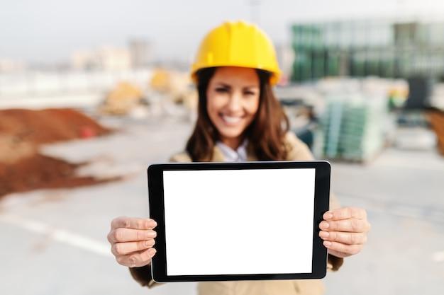 Bello architetto femminile sorridente con il casco sulla compressa capa della tenuta mentre stando al cantiere. messa a fuoco selettiva su tablet.