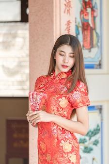 Bello asiatico della donna che porta vestito rosso durante il nuovo anno cinese