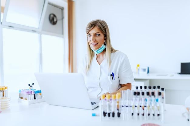 Bello assistente di laboratorio biondo femminile caucasico che si siede allo scrittorio e che per mezzo del computer portatile per l'immissione dei dati.