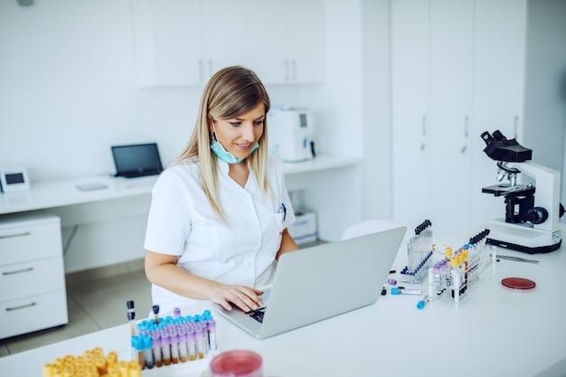 Bello assistente di laboratorio caucasico sorridente che si siede allo scrittorio e che per mezzo del computer portatile per l'immissione dei dati.