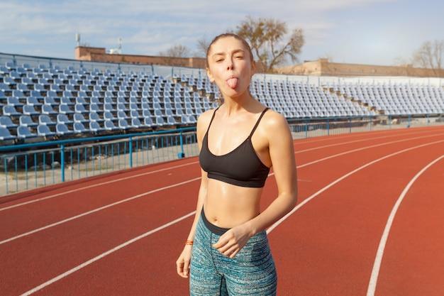 Bello atleta caucasico della ragazza che riposa dopo avere pareggiato su una pista corrente.