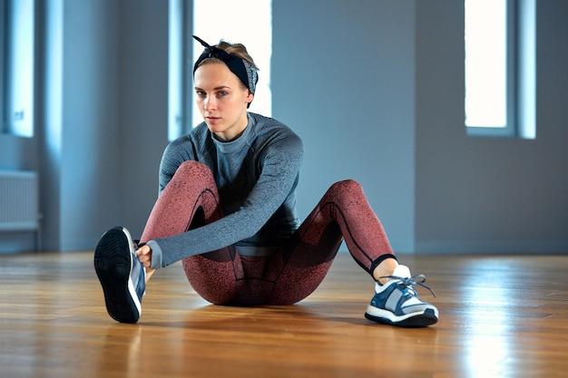 Bello atleta della giovane donna che lega i laccetti sulle scarpe da tennis mentre rilassandosi dall'allenamento di forza in palestra. oncept di fitness e sport