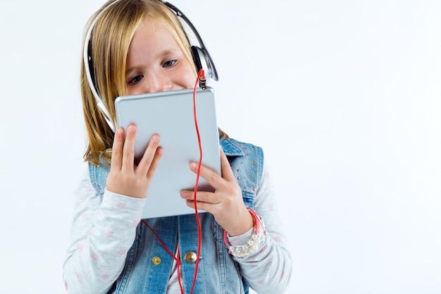 Bello bambino ascoltare musica con compressa digitale.