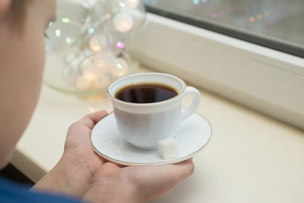 Bello bambino che beve tè e guarda attraverso la finestra mentre era seduto al davanzale della finestra a casa
