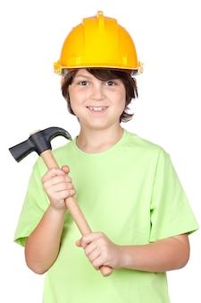 Bello bambino con il casco e martello gialli sopra una priorità bassa bianca