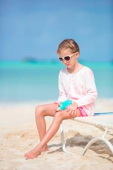 Bello bambino con la bottiglia di crema solare sulla spiaggia tropicale