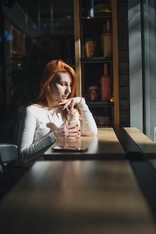 Bello barattolo del frullato della tenuta della giovane donna nel caffè