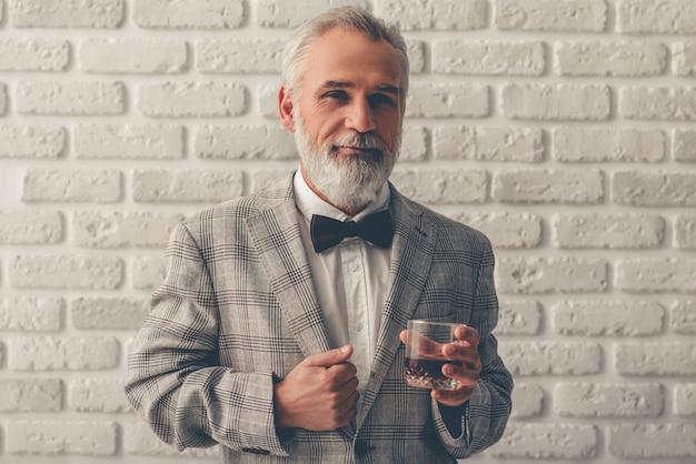 Bello barbuto tiene in mano un bicchiere di whisky