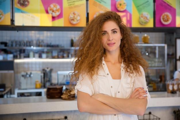 Bello barista dai capelli rossi femminile che esamina macchina fotografica e sorridere