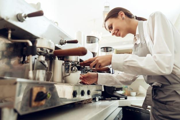 Bello barista della ragazza che prepara caffè