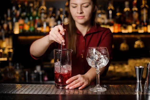Bello barista femminile che mescola bevanda alcolica dolce con ghiaccio