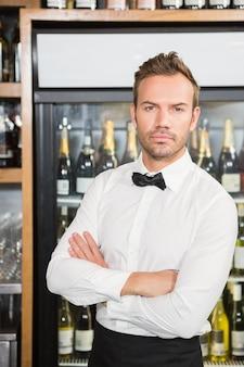 Bello barman incrociando le braccia
