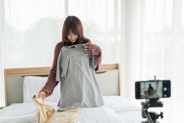 Bello blogger asiatico della donna che mostra i vestiti sulla macchina fotografica alla registrazione del video del vlog