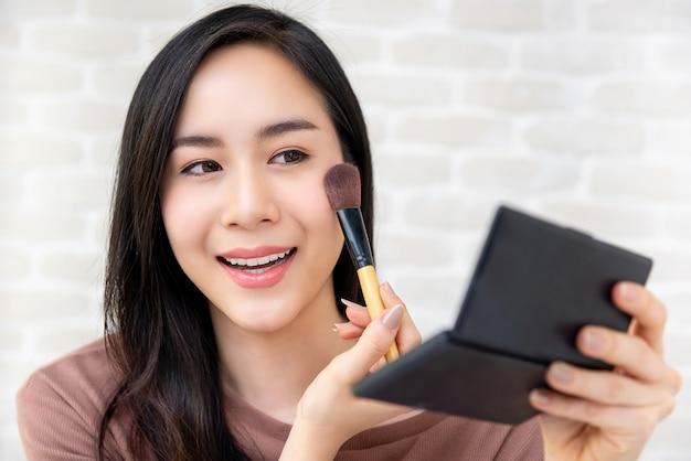 Bello blogger asiatico di bellezza della donna che fa esercitazione cosmetica di trucco
