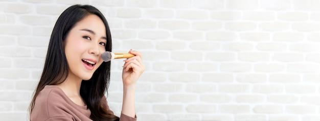 Bello blogger asiatico di bellezza della donna che fa esercitazione di trucco