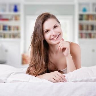 Bello brunette romantico della ragazza / della donna che si trova sul letto nella sua stanza a casa