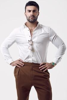 Bello brutale uomo d'affari abbronzato in una camicia bianca e occhiali da sole