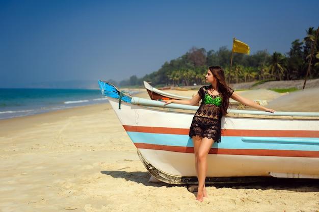 Bello castana sexy sulla spiaggia sabbiosa tropicale vicino alla barca di legno sul fondo blu del mare e sul chiaro cielo il giorno soleggiato caldo