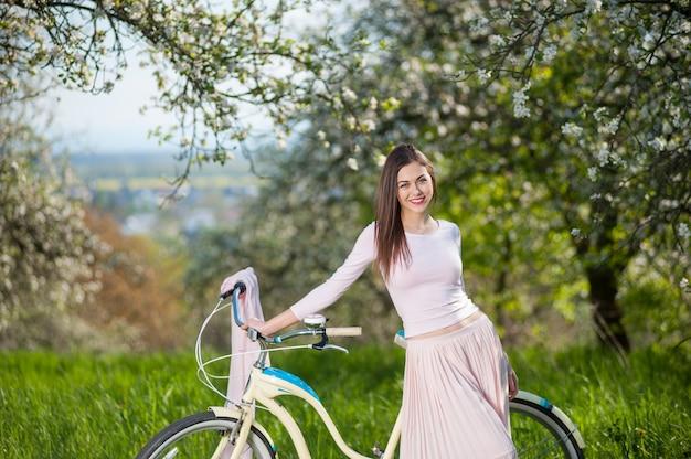 Bello ciclista femminile con la retro bicicletta in primavera giardino