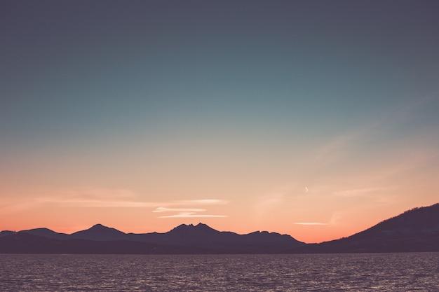 Bello cielo di tramonto dentellare sopra il silhourtte delle montagne sulla spiaggia.
