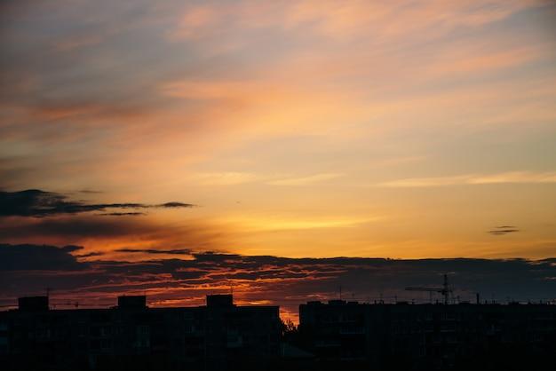 Bello cielo nuvoloso drammatico di mattina sopra la siluetta delle costruzioni della città
