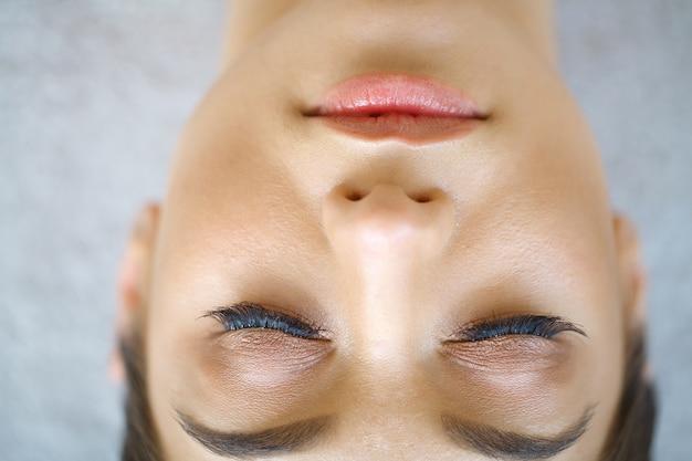 Bello colpo a macroistruzione dell'occhio femminile con ciglia lunghe estreme e trucco della fodera nera. trucco dalla forma perfetta e ciglia lunghe. cosmetici e trucco. colpo a macroistruzione del primo piano di volto degli occhi di modo