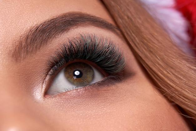 Bello colpo a macroistruzione dell'occhio femminile con ciglia lunghe estreme e trucco della fodera nera