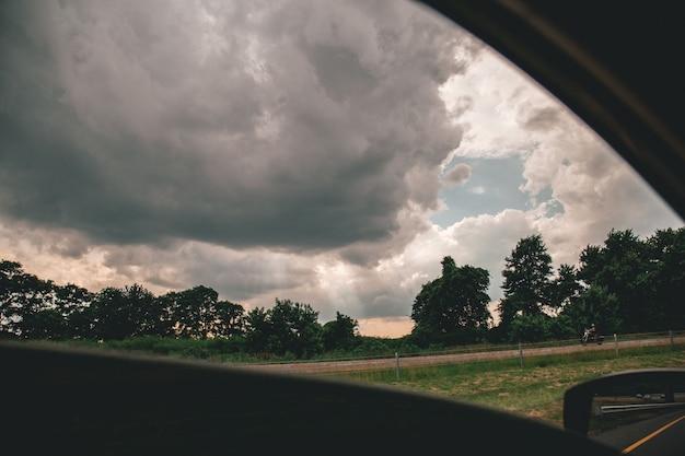 Bello colpo dei cieli nuvolosi sopra gli alberi presi da un'automobile