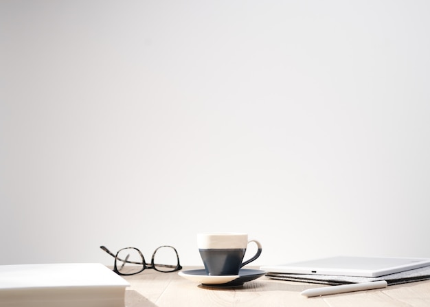 Bello colpo dei vetri ottici e una tazza su una tabella con una priorità bassa bianca e spazio per testo