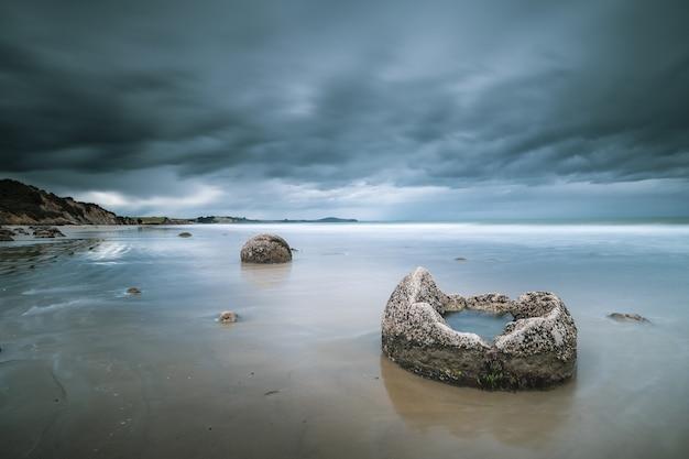 Bello colpo del mare con le rocce e le montagne nella distanza sotto un cielo nuvoloso blu