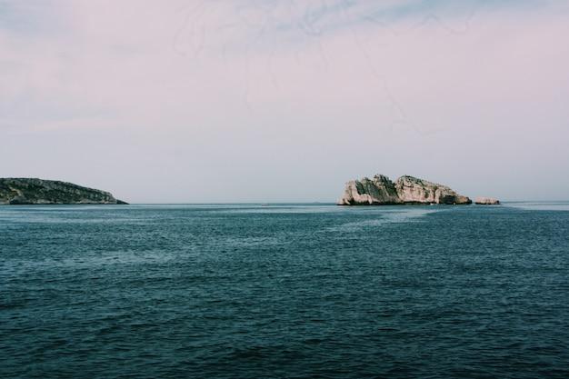 Bello colpo del mare con le rocce e le scogliere sotto un cielo nuvoloso