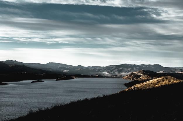 Bello colpo delle montagne su una riva del lago durante l'alba