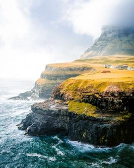 Bello colpo delle montagne verdi e del mare con il cielo nuvoloso
