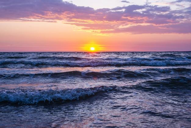 Bello colpo delle onde del mare sotto il cielo rosa e porpora con il sole che splende durante l'ora dorata