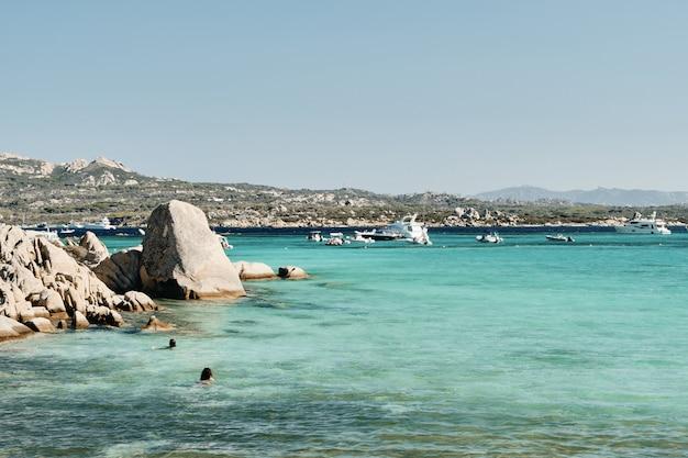 Bello colpo delle rocce nell'acqua con le barche e le montagne nella distanza sotto un cielo blu