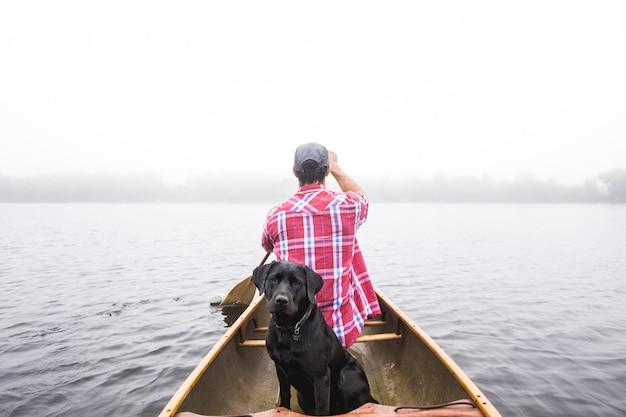 Bello colpo di un cane nero e di un maschio che navigano su una piccola barca sul corpo idrico