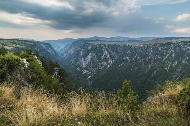 Bello colpo di un canyon nelle montagne e nel cielo nuvoloso