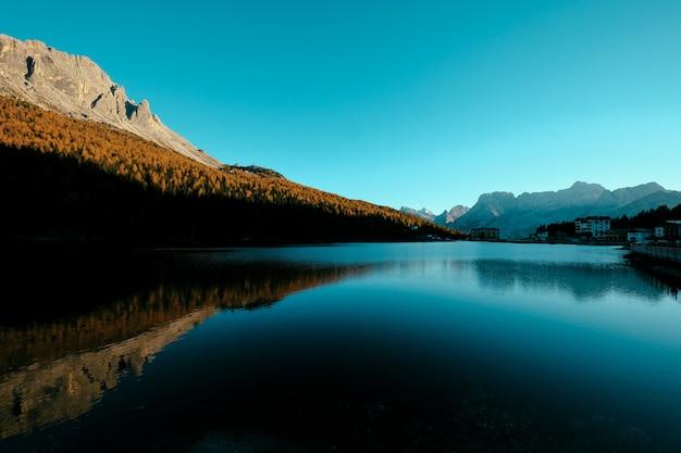 Bello colpo di un lago in mezzo agli alberi gialli sulla collina e sulla costruzione su una riva
